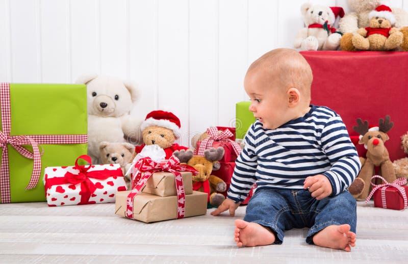 第一圣诞节:解开礼物-愉快的家庭的婴孩- chil 图库摄影