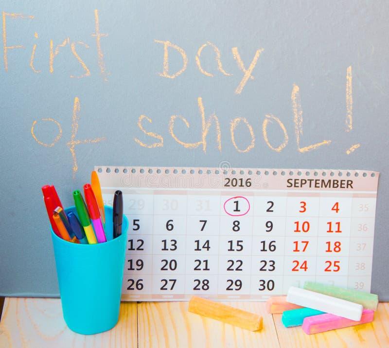 第一天在写在黑板的学校,日历,文具 免版税库存图片