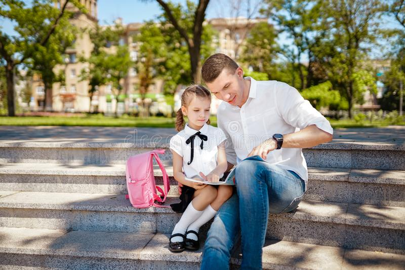 第一天在学校 父亲和小孩女儿坐台阶和读书,研究教训 父母身分和孩子 免版税图库摄影