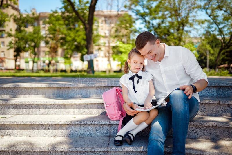 第一天在学校 父亲和小孩女儿坐台阶和读书,研究教训 父母身分和孩子 免版税库存照片