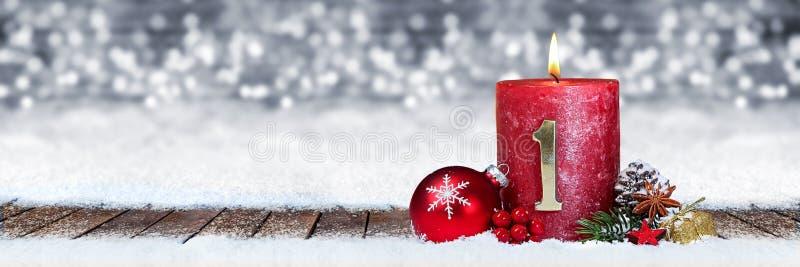第一星期天与金黄金属在木板条的第一的出现红色蜡烛在全景bokeh背景雪前面  库存照片