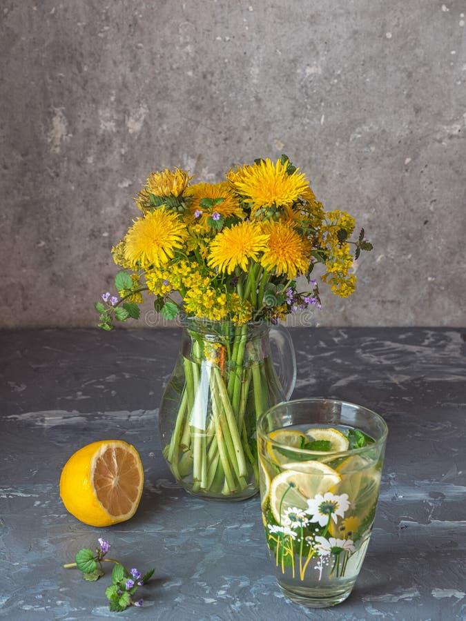 第一朵报春花的花束在一个玻璃水罐和一汽水的用柠檬和香蜂草 开花的黄色蒲公英,油菜和 库存图片