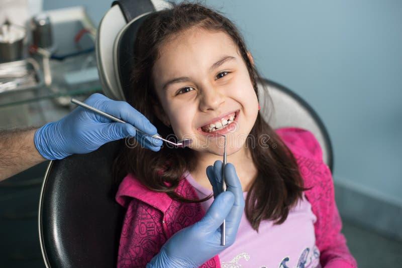 第一次牙齿参观的女孩 做患者的资深男性牙医第一核对在牙齿办公室 免版税库存照片