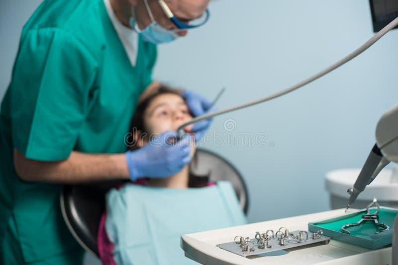 第一次牙齿参观的女孩 对待耐心女孩牙的资深小儿科牙医在牙齿办公室 免版税图库摄影