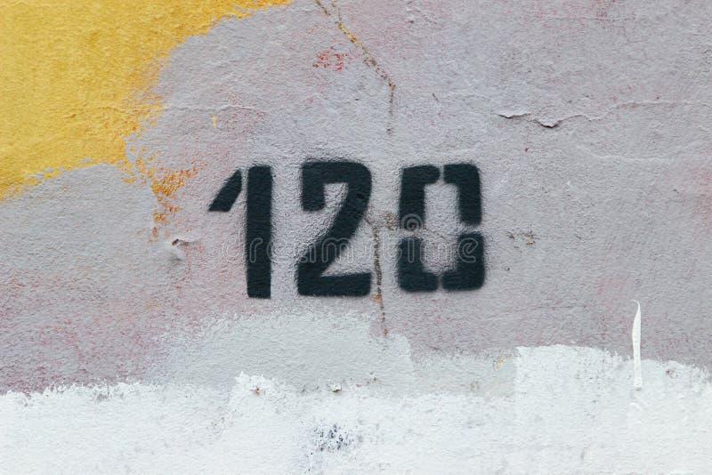 第一百和二十120 在老墙壁上的黑字法 图库摄影