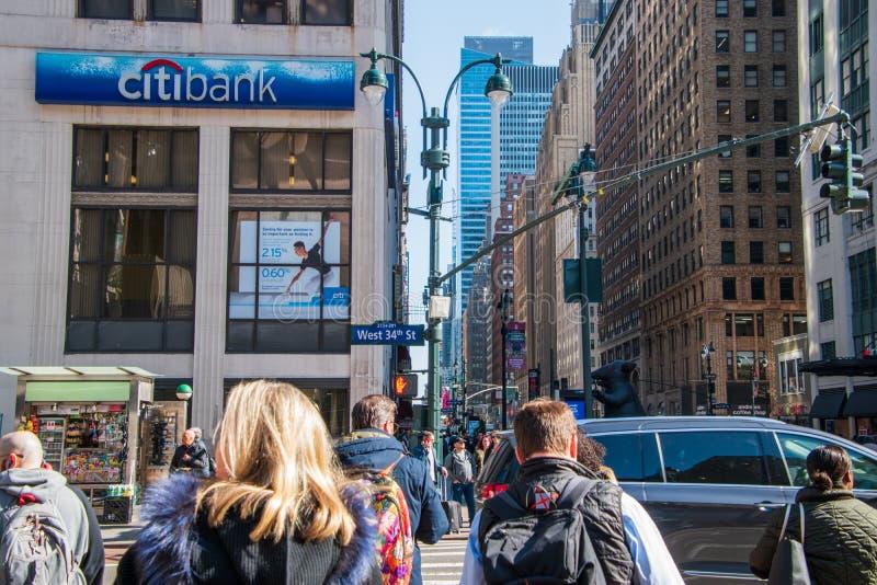 第七条大道的看法在第34个街道交叉点在曼哈顿,有人和一个标志人群的纽约花旗银行的 库存图片