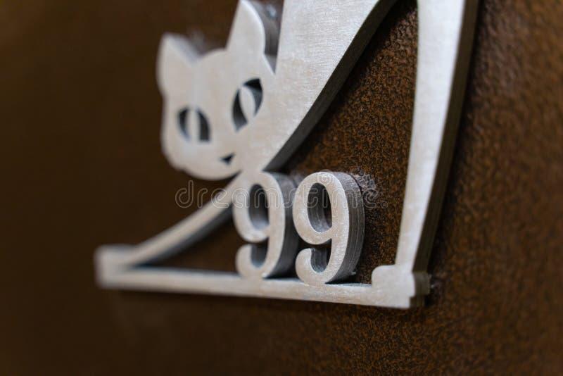 第九十九和在金属大门的一只猫 免版税库存图片