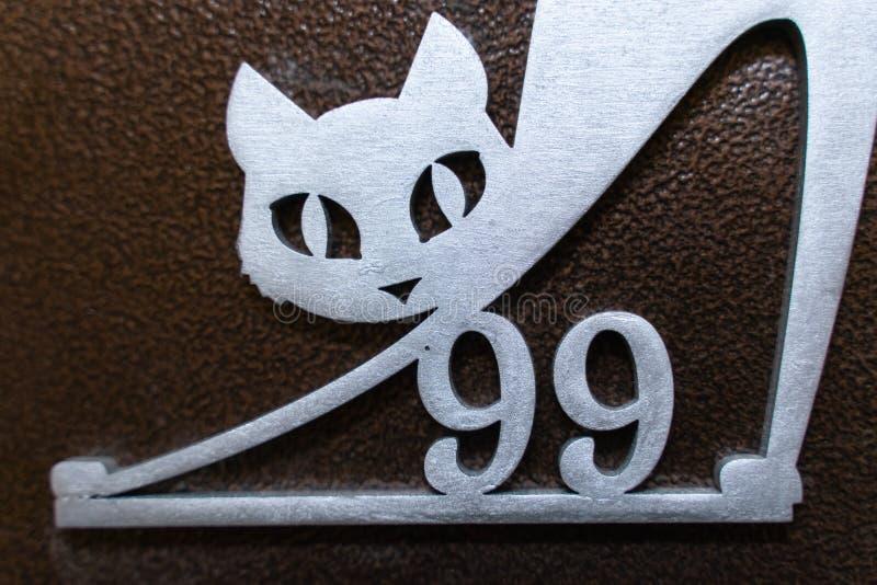第九十九和在金属大门的一只猫 图库摄影