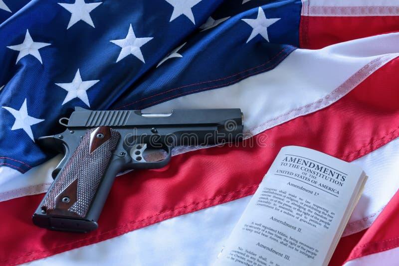 第二校正和枪枝管制在美国,概念 一把手枪和美国宪法在美国旗子 免版税库存图片