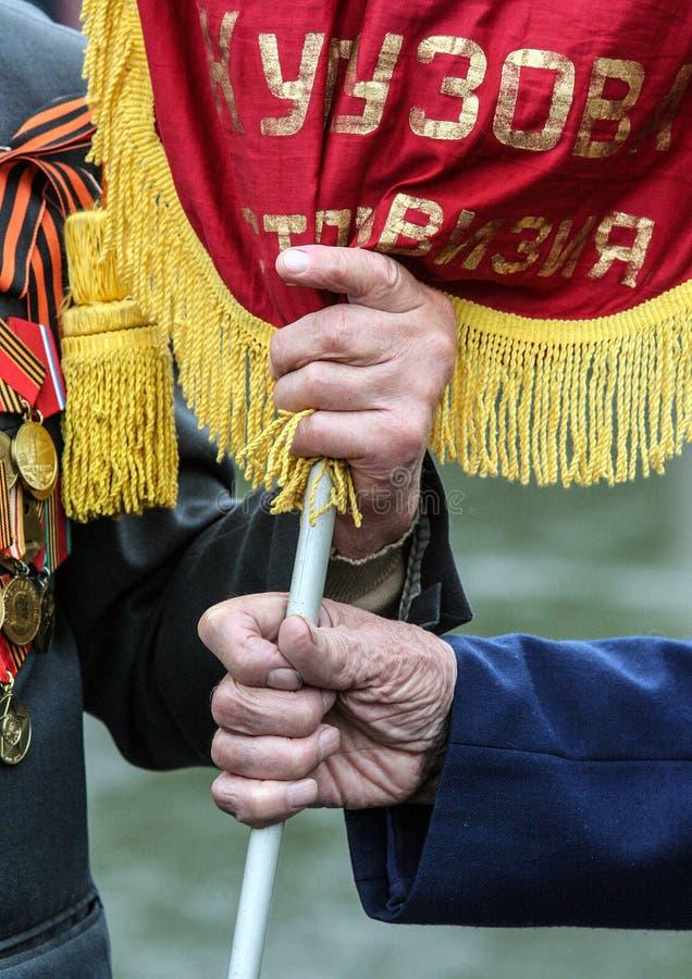 第二次世界大战关闭的退伍军人 庆祝日莫斯科胜利 拿着旗子的退伍军人的手 图库摄影