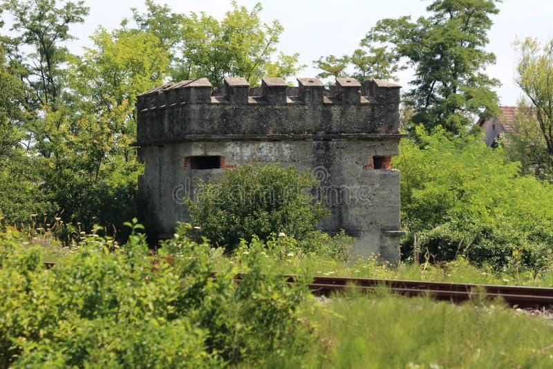 第二次世界大战小具体地堡被塑造象城堡被放弃在铁路轨道旁边和围拢与长得太大的树和为 免版税图库摄影