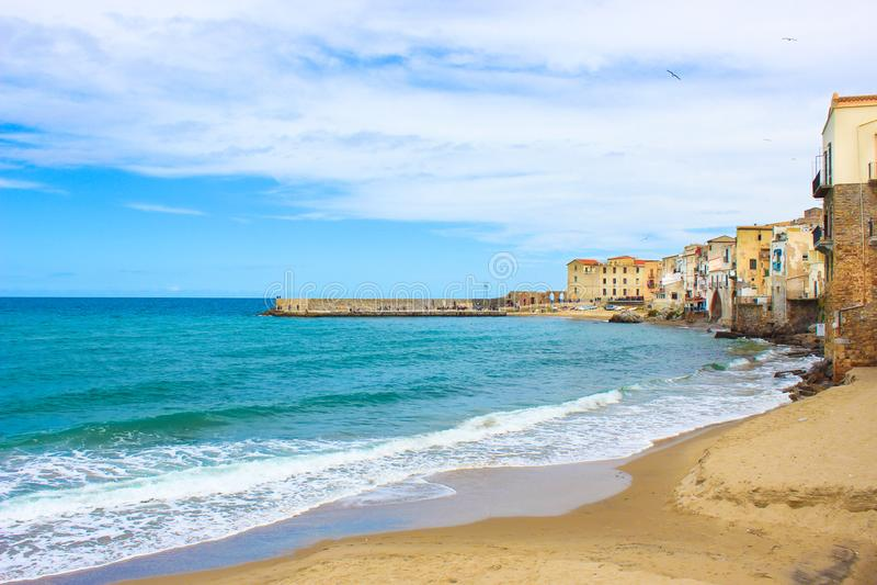 第勒尼安海海岸的美丽的老房子在西西里人的切法卢,意大利 有沙滩的小历史城市 图库摄影