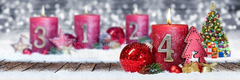 第四星期天与金黄金属在木板条的第一的出现红色蜡烛在银色bokeh背景雪前面  免版税库存照片