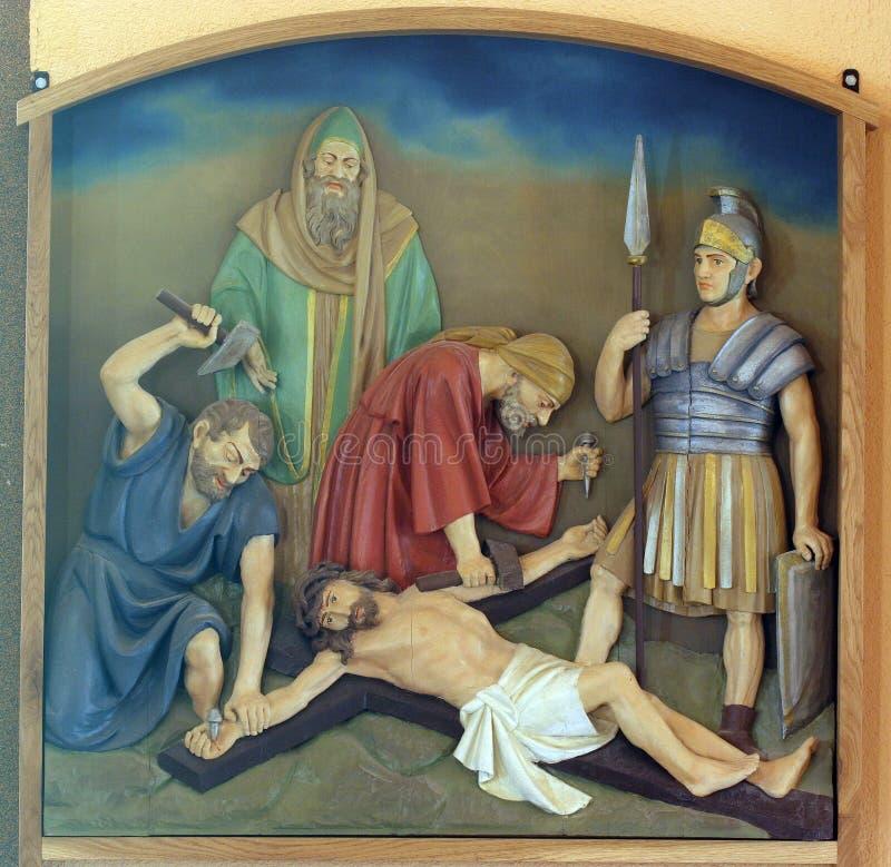 第11个苦路,在十字架上钉死:耶稣被钉牢对十字架 库存照片