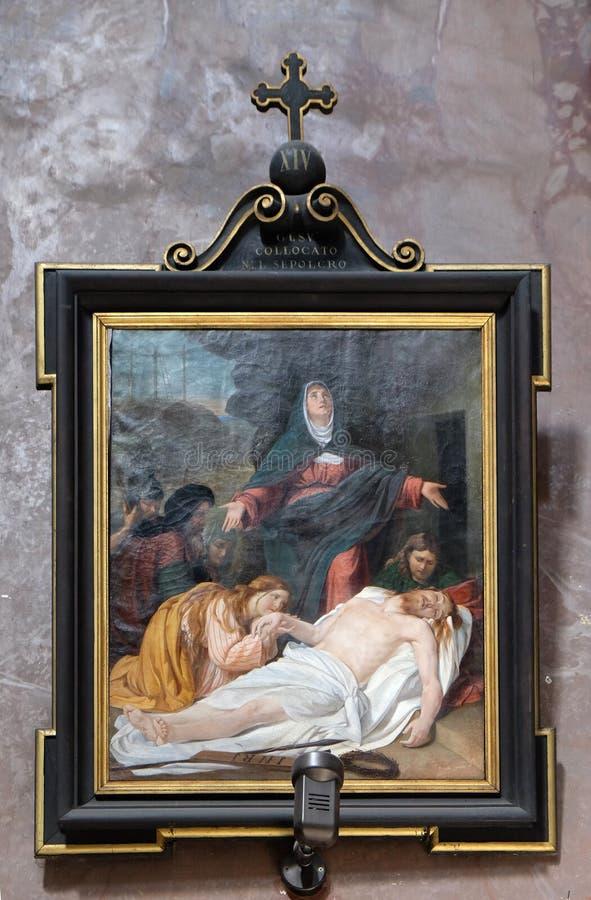 第14个苦路,耶稣在坟茔在香火被放置并且被盖 图库摄影