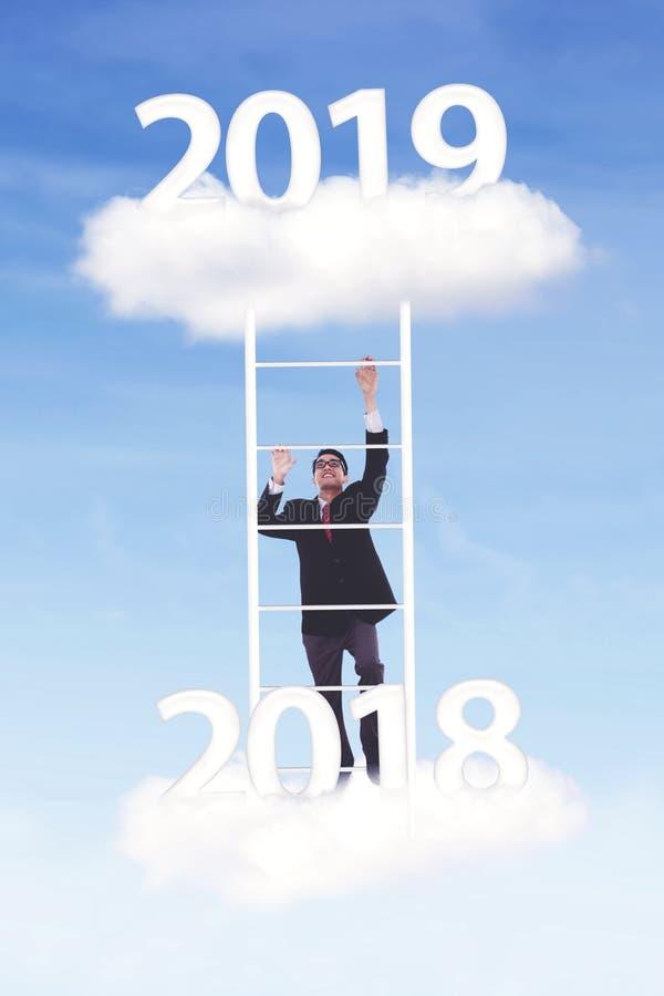 第2019年的年轻商人攀登 免版税图库摄影