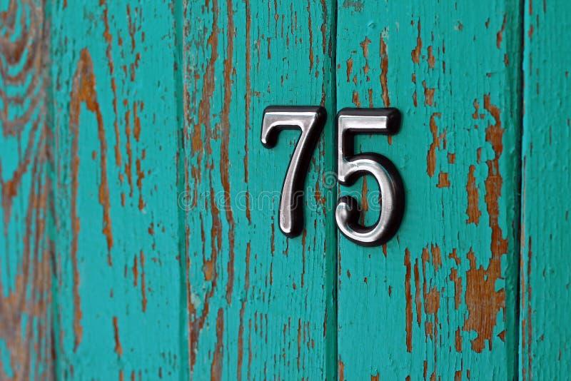 第75的图象在木破旧的墙壁上的 免版税库存图片