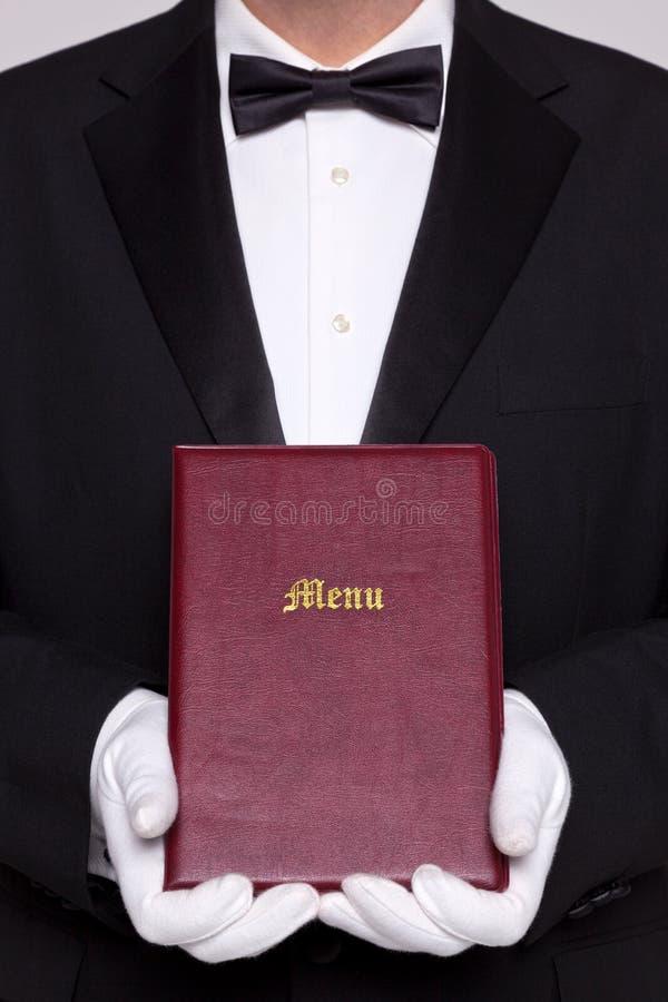 等候人员在两个现有量中的拿着一个菜单 免版税库存图片