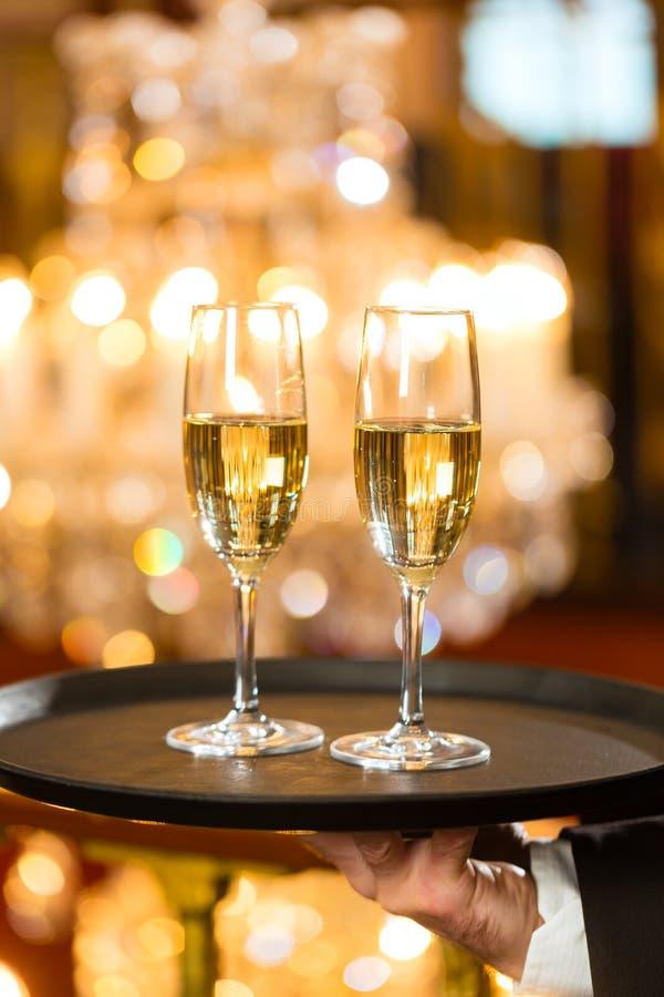 等候人员在餐馆服务在盘的香槟玻璃 免版税库存照片