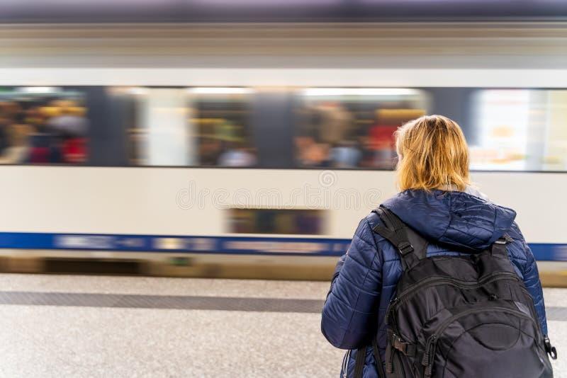 等待一列火车的妇女在无法认出的地铁,行动迷离 库存图片