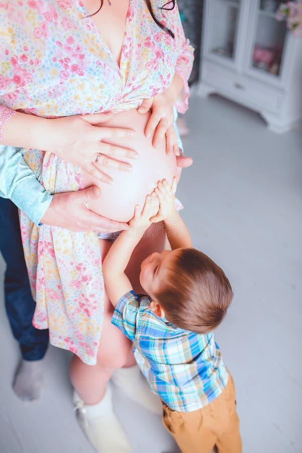 等待他的姐妹,男孩接触他的肚子 免版税库存图片