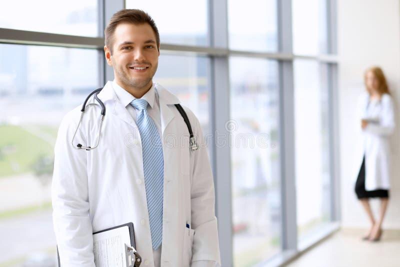 等待他的队的微笑的医生,当站立挺直时 免版税图库摄影