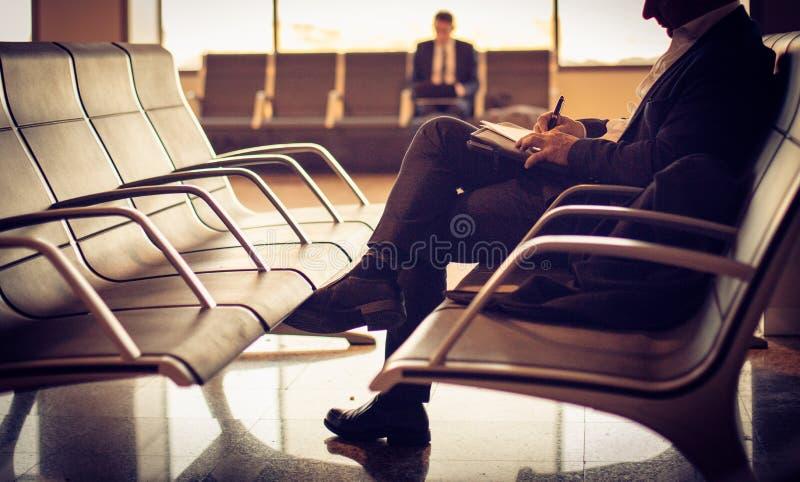 等待他的飞行 人在机场 免版税库存图片