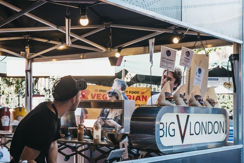 等待他的食物的人在大V伦敦停留演出地在自治市镇市场,伦敦,英国上 免版税库存照片