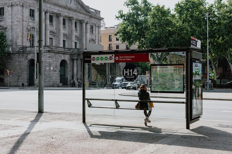 等待公共汽车的单独女孩 免版税库存照片