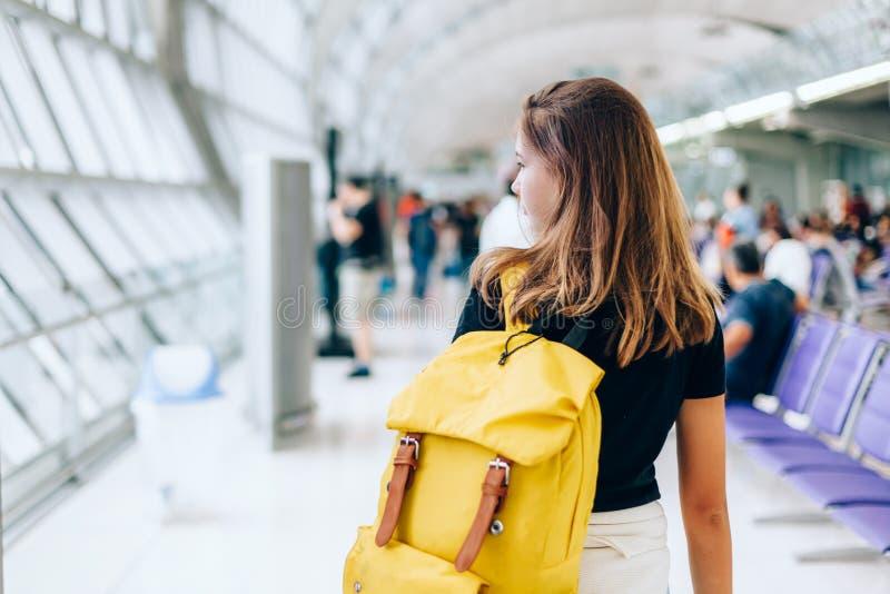 等待国际航班的青少年的女孩在机场离开终端 免版税库存照片