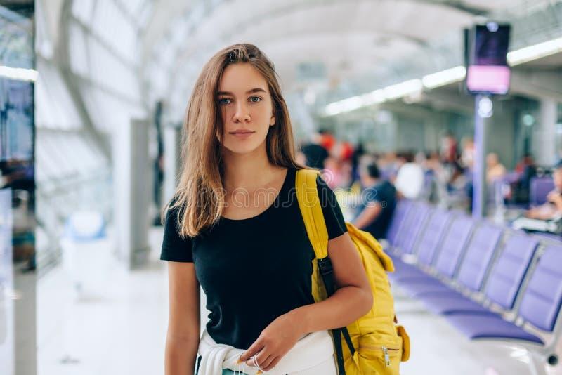 等待国际航班的青少年的女孩在机场离开终端 免版税库存图片