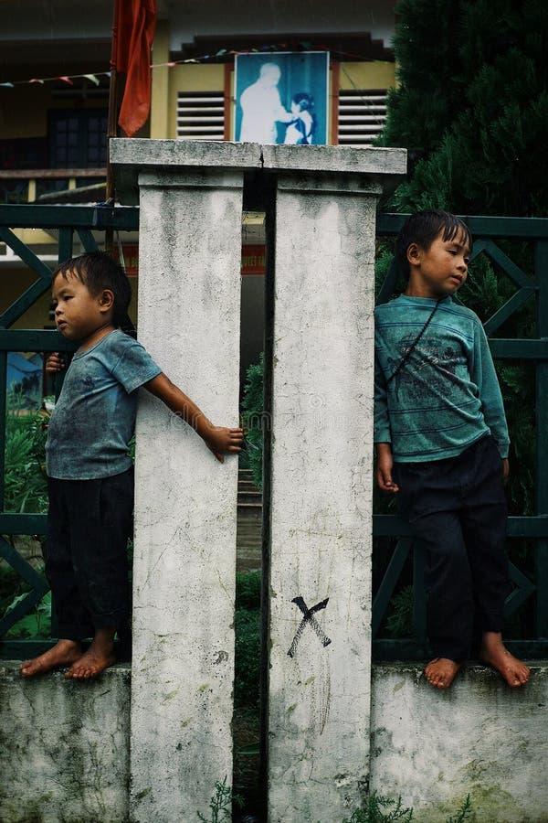 等待在他们的学校前面的小孩在山村 免版税库存照片