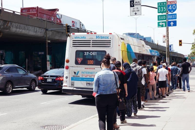 等待在公交车汽车站的队列的人们上公共汽车在蒙特利尔,魁北克,加拿大 库存图片
