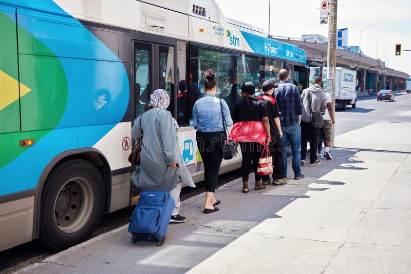 等待在公交车汽车站的队列的人们上公共汽车在蒙特利尔,魁北克,加拿大 库存照片