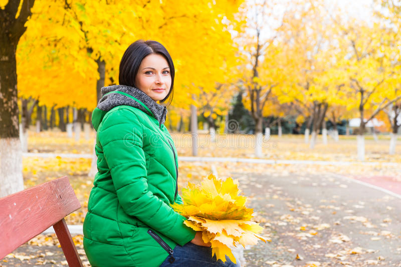 等待在公园长椅的可爱的妇女 免版税库存照片