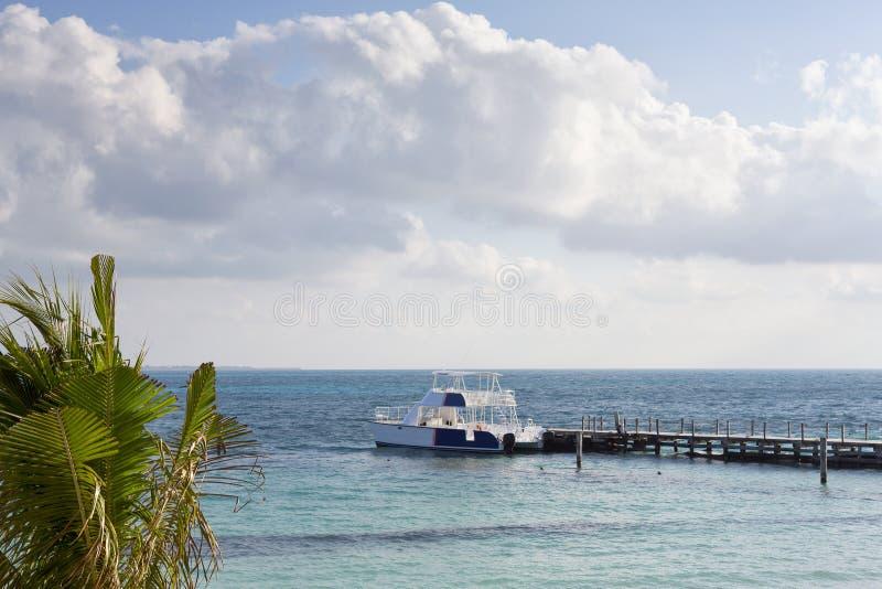 等待在加勒比海洋岸的码头的大小船 库存图片