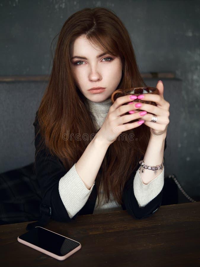 等待在咖啡馆的一名逗人喜爱的俏丽的红头发人妇女的画象享受时间与一个智能手机的咖啡休息在桌藏品工艺 免版税图库摄影