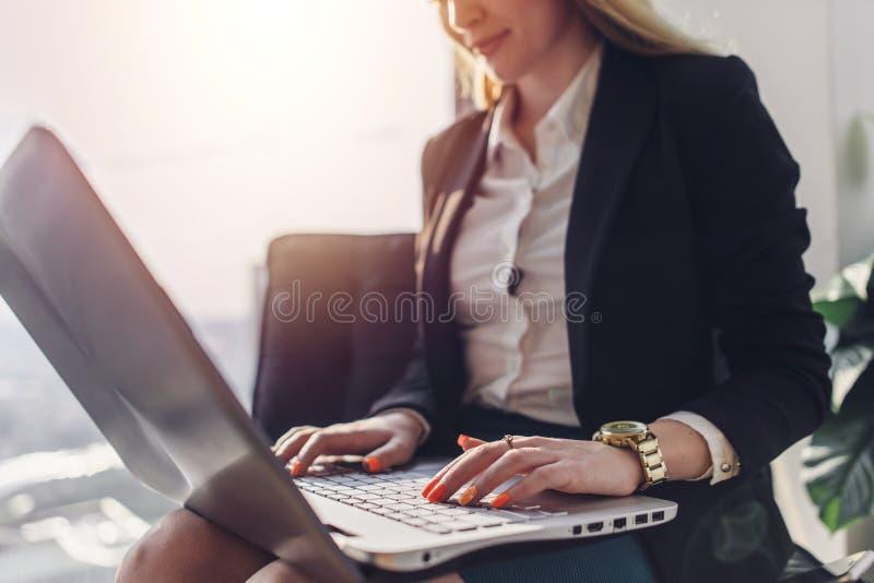 等待在大厅里的少妇在运作现代的办公室在谈话的膝上型计算机坐电话 库存照片