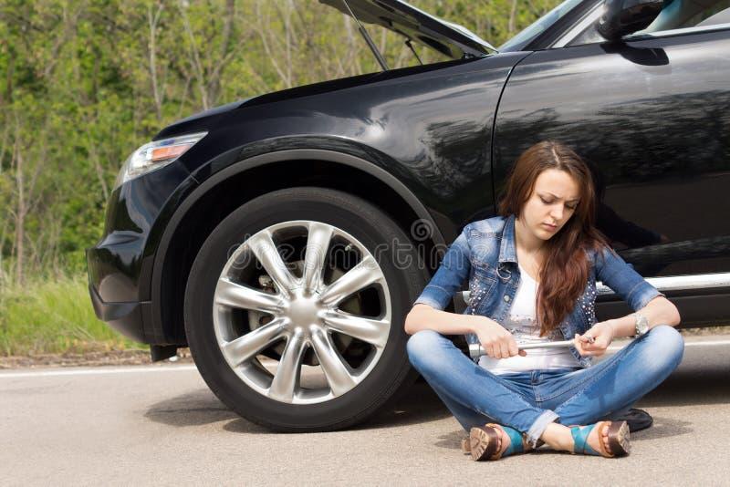 等待在她旁边失败的汽车的妇女 图库摄影
