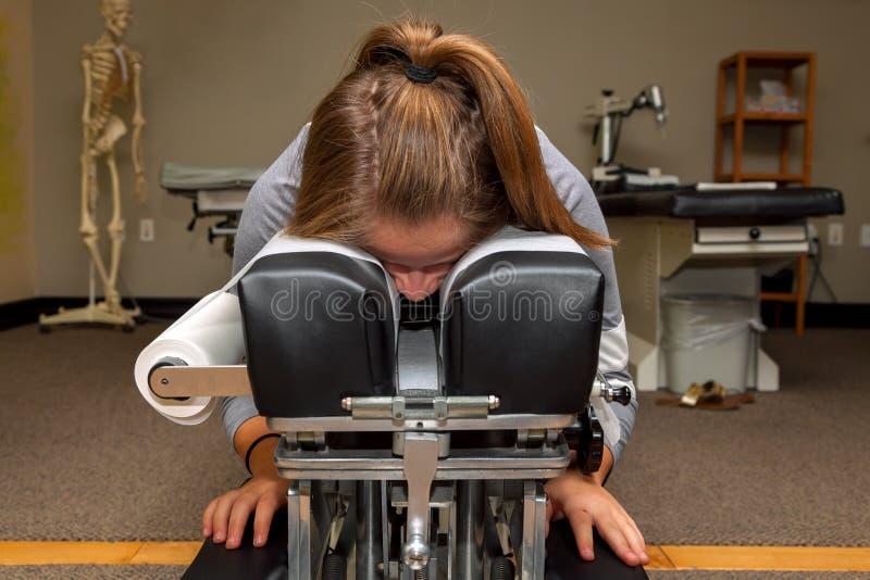 等待在她的胃Ther的掀动的按摩脊柱治疗者表上的女孩 免版税库存照片