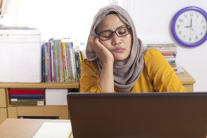 等待在她的膝上型计算机前面的疲乏的困回教女实业家 图库摄影