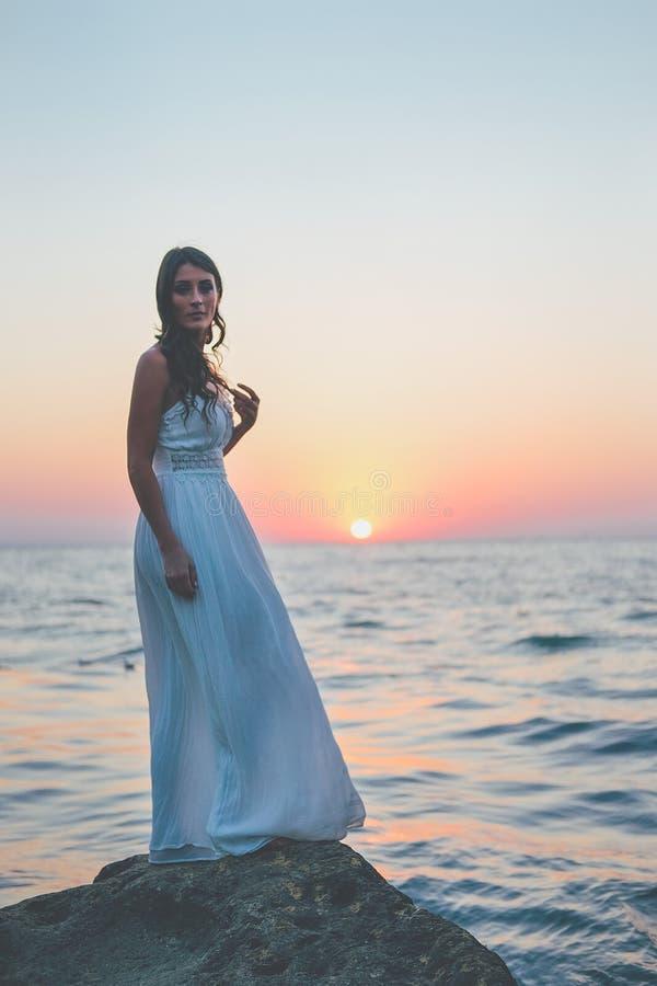等待在岸的白色礼服的浪漫女性妇女 免版税库存照片