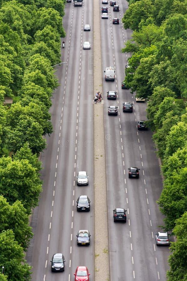 等待在有通过从在几条车道的勃兰登堡门,与绿色树的鸟瞰图的汽车的繁忙的路中间的骑自行车者 免版税库存照片