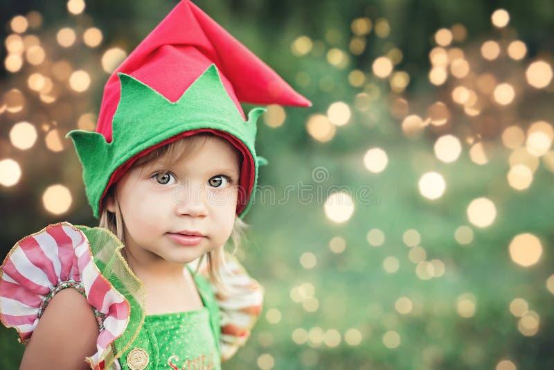 等待在木头的孩子圣诞节在juli 小孩画象在圣诞树附近的 装饰圣诞树的女孩 免版税库存图片