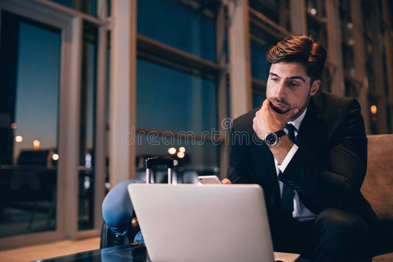 等待在机场休息室和看膝上型计算机的商人 库存图片