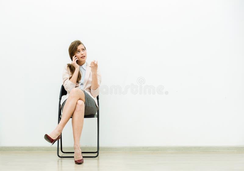 等待在椅子的办公室成套装备的妇女 库存图片