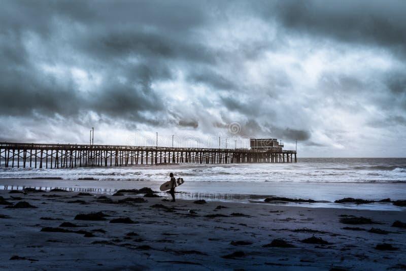 等待在海岸线的冲浪者拿着他的委员会在一多云天 免版税图库摄影