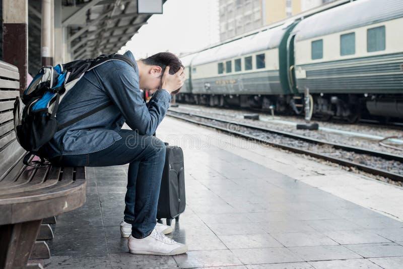 等待在火车站的亚裔沮丧的旅客在差错以后 图库摄影