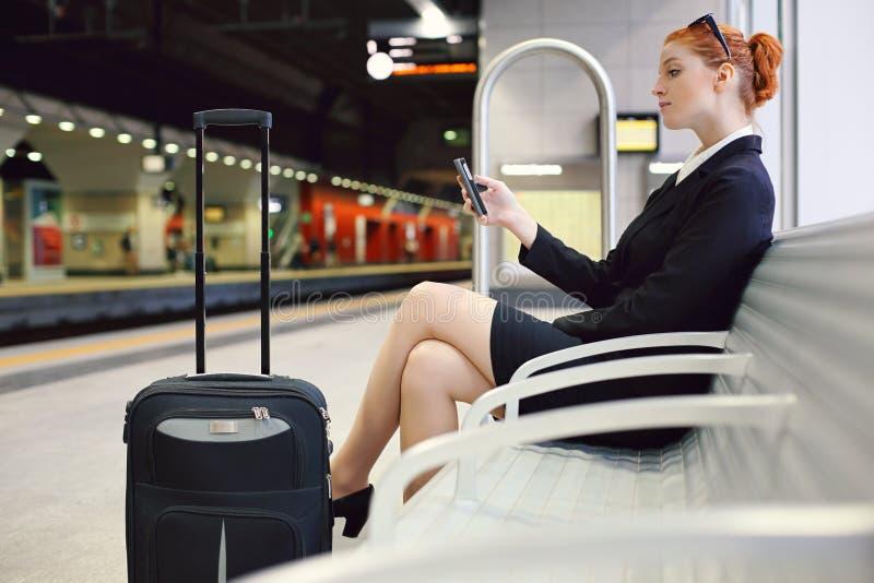 等待在火车站的美丽的女实业家 免版税库存图片