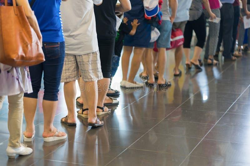 等待在登机门的亚裔人民特写镜头队列在机场 免版税库存图片